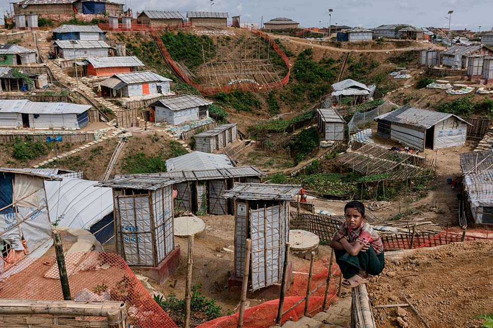 a child sits atop a fence overlooking a Rohingya refugee camp in Bangladesh