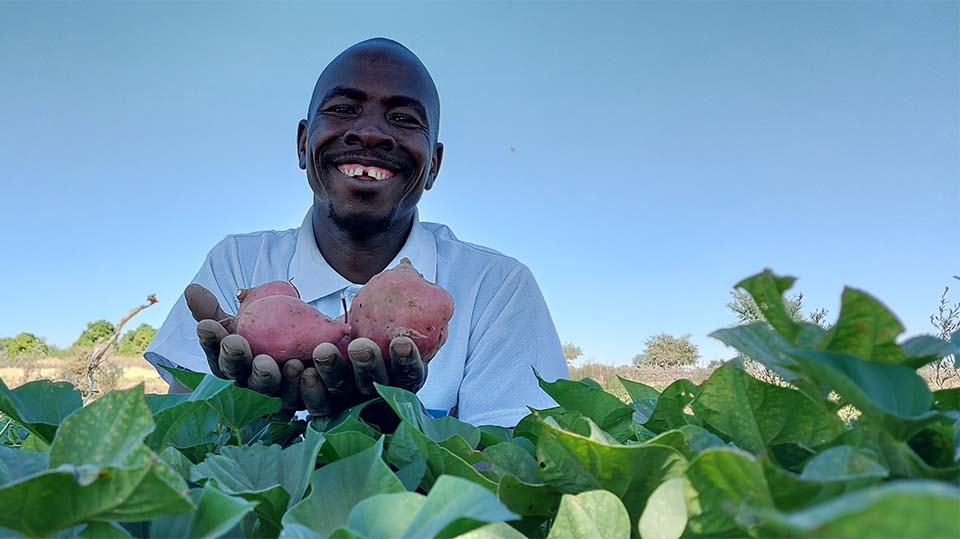 Sudanese community extension worker holding crops