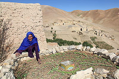 Bonu, a mother of three from Afghanistan's Ghor province, weeds her new keyhole garden. She looks forward to her first harvest and the nutritious meals she will prepare with recipes from Catholic Relief Services. Photo by Jennifer Hardy/CRS