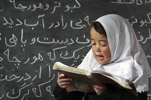 A young girl reads in a classroom established by CRS in Afghanistan's Ghor Province. Photo by Nikki Gamer/CRS