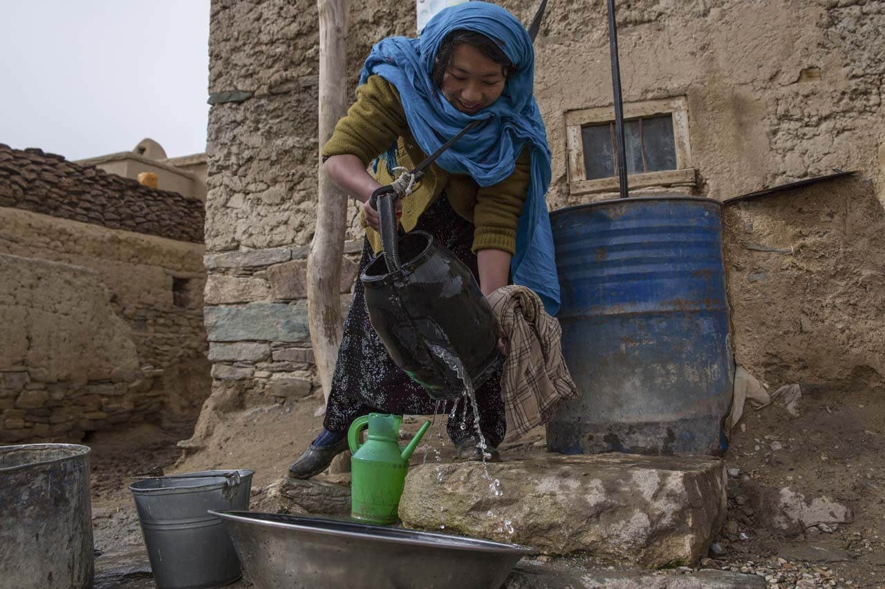 woman collects water in Afghanistan