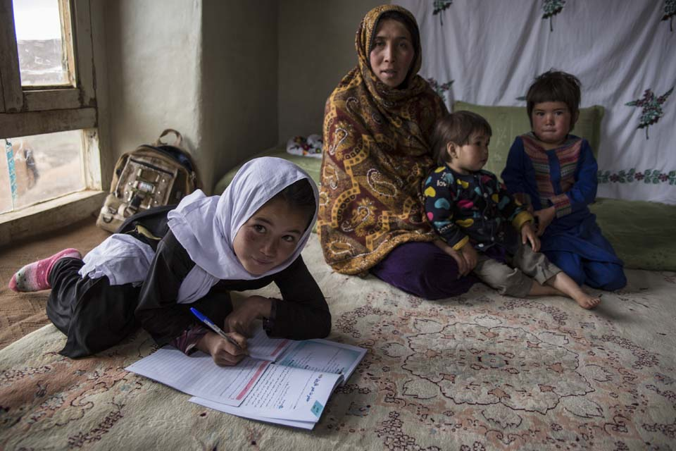 Afghanistan girl with homework and family