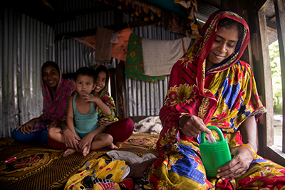 Rina Begum adds money to her family's savings box. CRS and Caritas Bangladesh are working with Rina's family to build a plan to bounce back from disasters. Photo by Jennifer Hardy/CRS