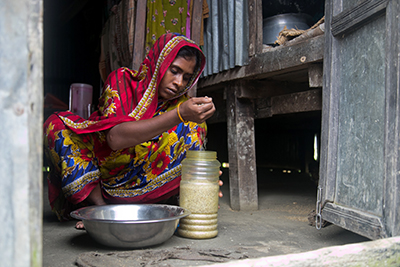 Rina Begum stores rice in a watertight container. This will ensure her family has food to eat when the next cyclone hits. Photo by Jennifer Hardy/CRS