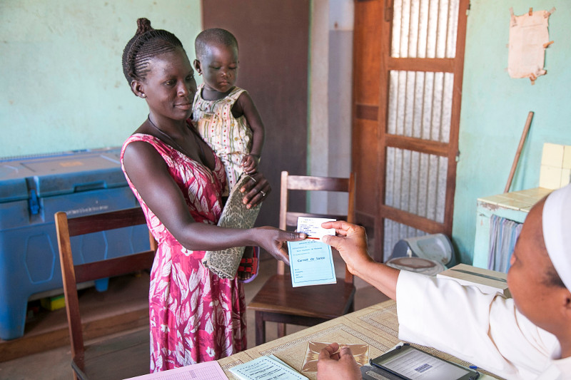 Immaculee Gnangui and her daughter Laurencia Akomahaou seek medical care at Centre de Sante: Chabicouma in Chabicouma, Benin. Immaculee uses micro-health insurance through a project organized by Catholic Relief Services.