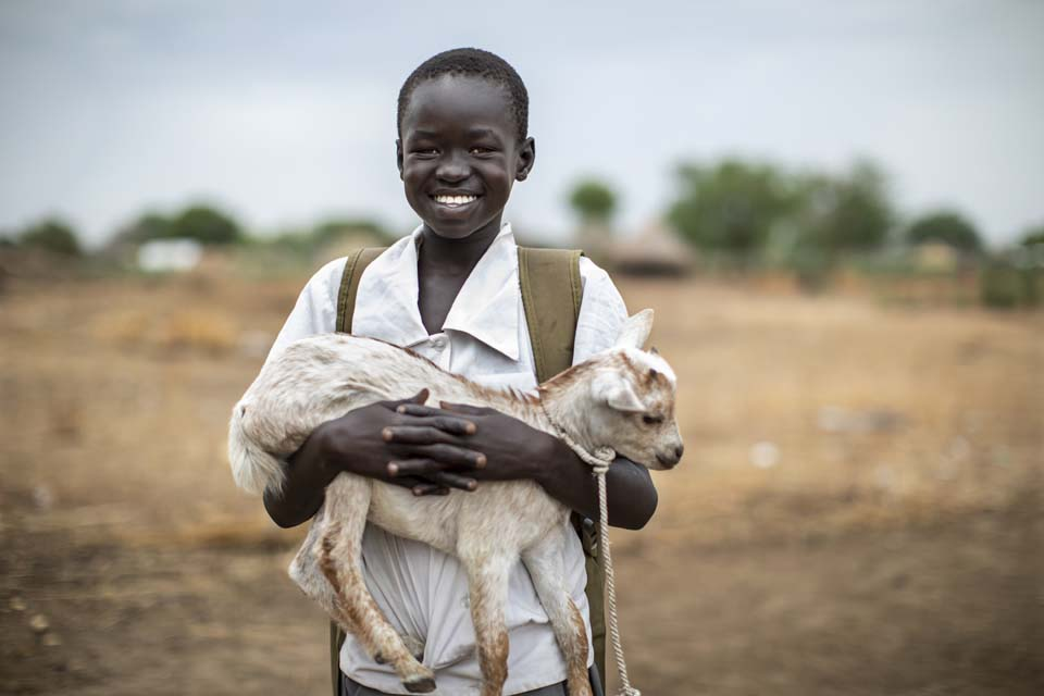 boy holds goat in South Sudan