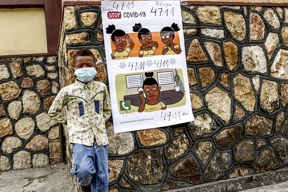 boy stands near covid poster in DR Congo