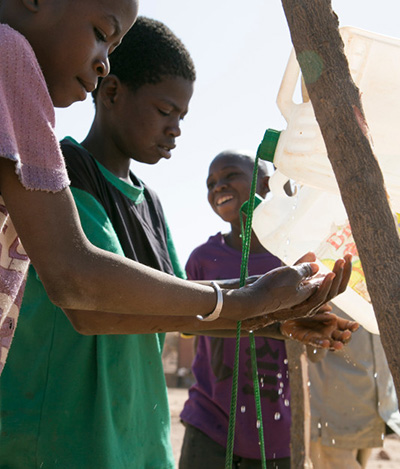 """Students use a \""""tippy tap\"""" to wash their hands at a school in Burkina Faso. Photo by Michael Stulman/CRS"""