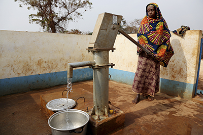 Every morning, Adidja Anina collects water for drinking and household use from a community pump in Eastern Cameroon. Photo by Michael Stulman/CRS