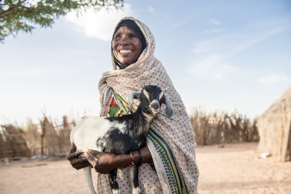 woman holding young goat