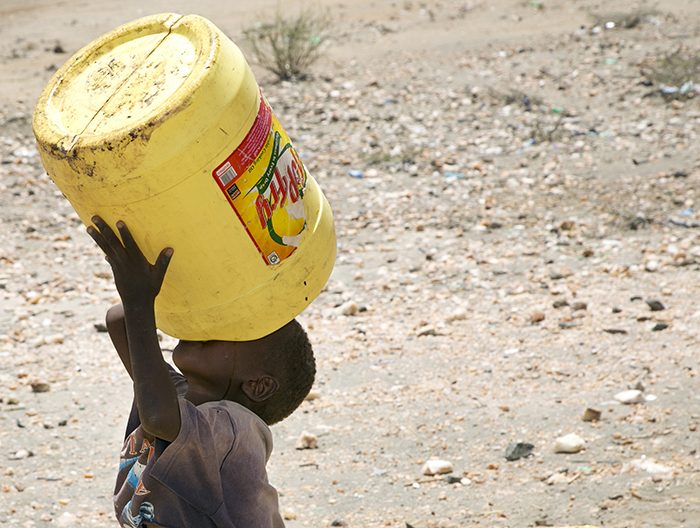 a child drinks from a large water container in Kenya