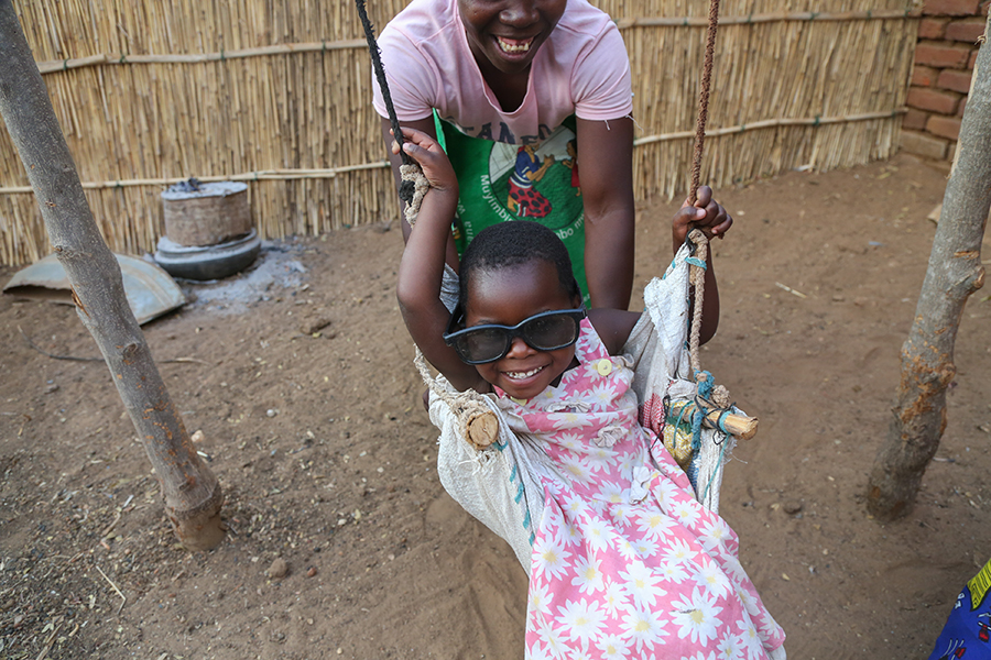 child in swing wearing big sunglasses in Malawi