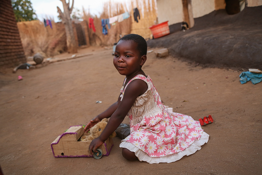 child playing with homemade toy in Malawi