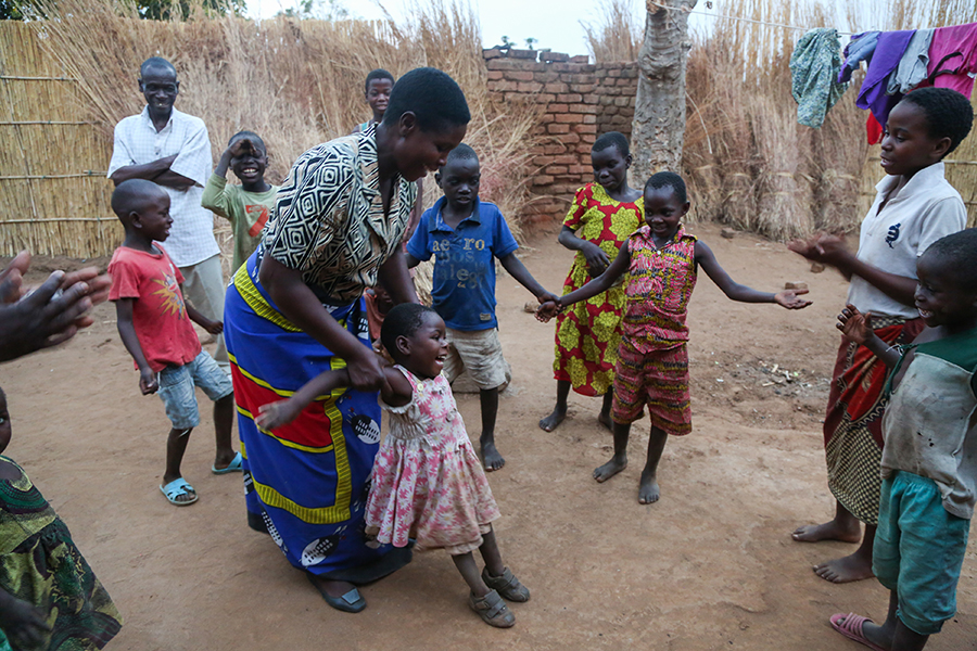 child stands with assistance in Malawi