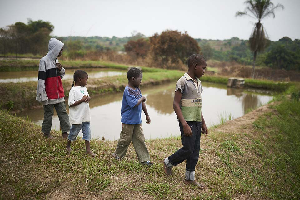 children in Republic of Congo walk past pond