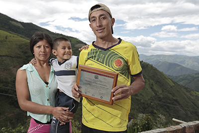 Fidencio Chamorro, with his wife and son in Colombia, displays the Borderlands certificate he received for growing the best coffee in 2013. Photo by Oscar Leiva/Silverlight for CRS