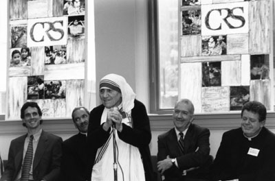 Mother Teresa speaks during her 1996 visit to CRS headquarters with, from left to right, Sean Callahan, Bishop John Ricard, Ken Hackett and Father Brian McCullough looking on. Photo by CRS staff