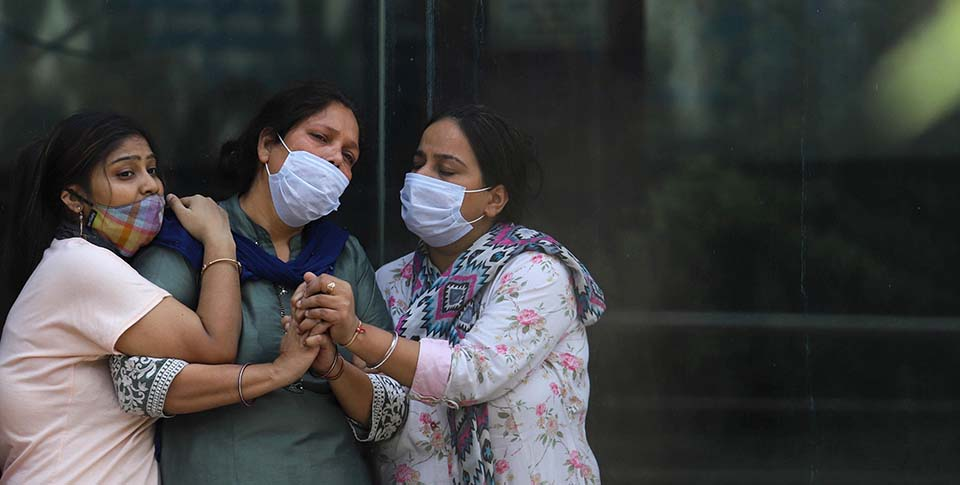 3 women in India wearing masks at crematorium
