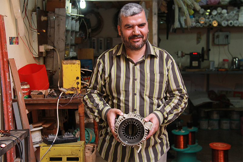 """Mohammed is working on an engine in the Cairo repair shop he opened. """"I want to thank CRS for giving me a new beginning,"""" he says."""
