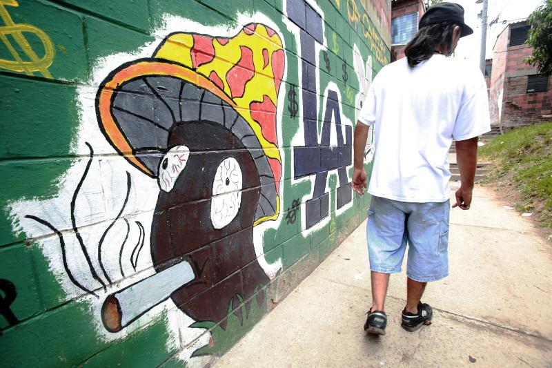 A beneficiary of CRS assisted program Jovenes Constructores walks by graffiti in High Risk Community Condominios Atlanta in San Salvador, El Salvador.