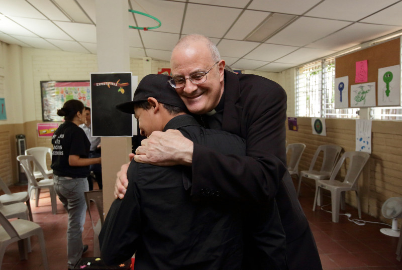 Bishop Gregory John Mansour of Brooklyn, New York, embraces Manuel,* a former gang member, during a recent visit to El Salvador. Photo by Silverlight for CRS
