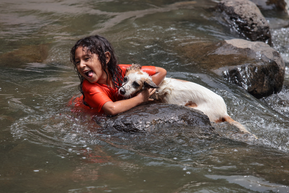 girls swims with dog in El Salvador