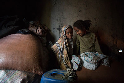 Yidenek, 4, and Tarkiua, 8, sit on top of bags of the teff their mother uses to make injera, a traditional Ethiopian flatbread. Their mother will use her earnings to send them to school. Photo by Sara A. Fajardo