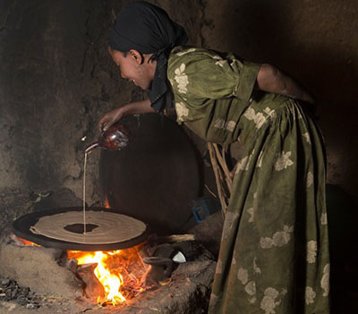 Abaynesh Legesse prepares traditional injera for sale in her kitchen in Benben Village, Ethiopia. She has seen her restaurant business increase five-fold since taking out a $50 loan for ingredients. Photo by Sara A. Fajardo