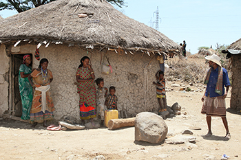 Jemal Bedhaso's wife and children seek shade outside their home. A CRS project is helping their village of Meiso cope with climate change. Photo by Kim Pozniak/CRS