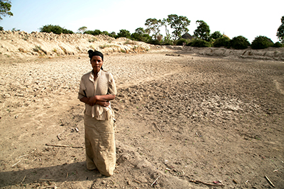 Badoo Fukura stands at the bottom of a basin that used to be the community watering hole. It served about 30 different families before going dry in October. Photo by Nancy McNally/CRS