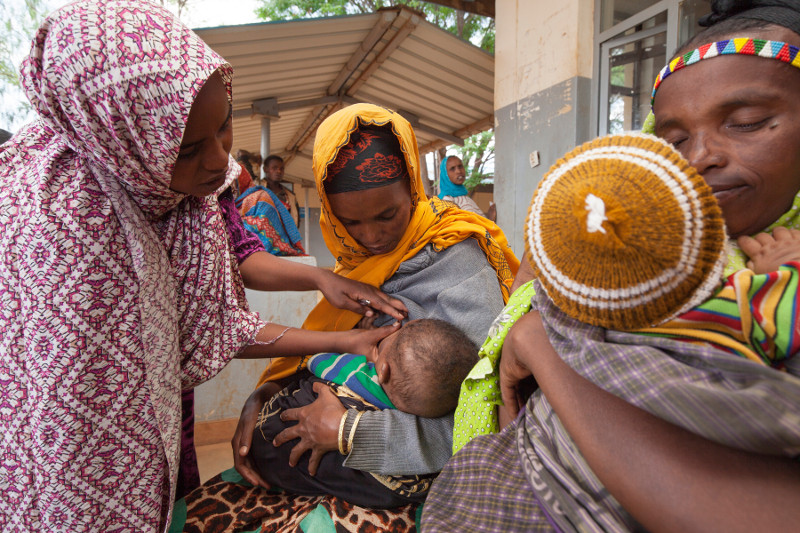 Samia Abrahim, standing,  helps Kadija Abdelahi, her baby Amar Yusuf, and other mothers learn about nutrition and the benefits of breastfeeding.