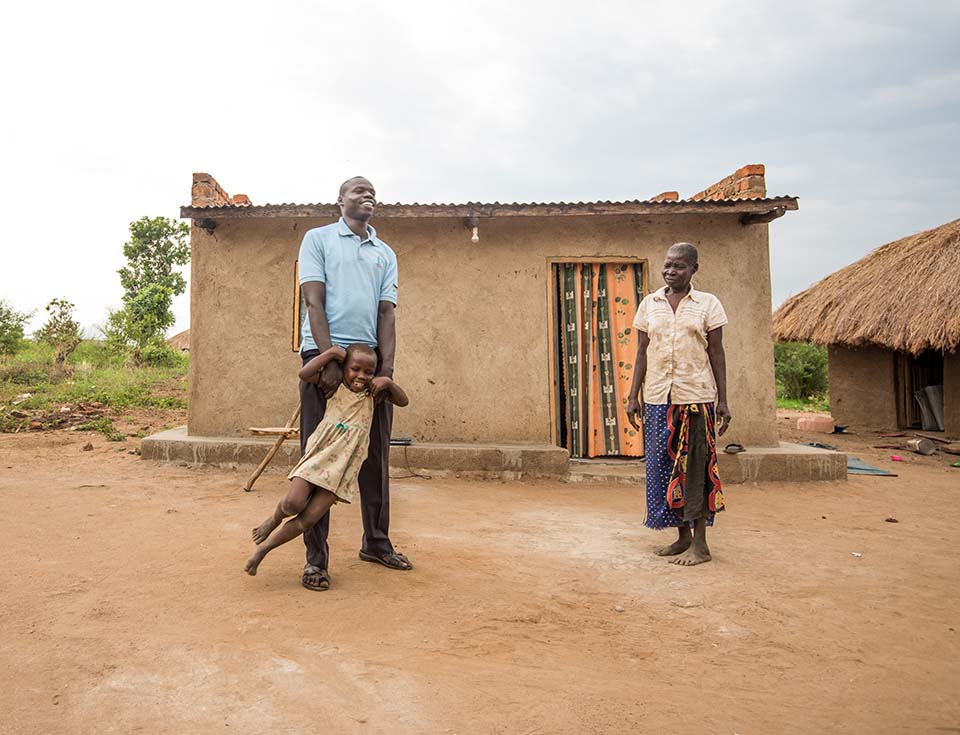 South Sudanese father plays with daughter outside their Uganda home