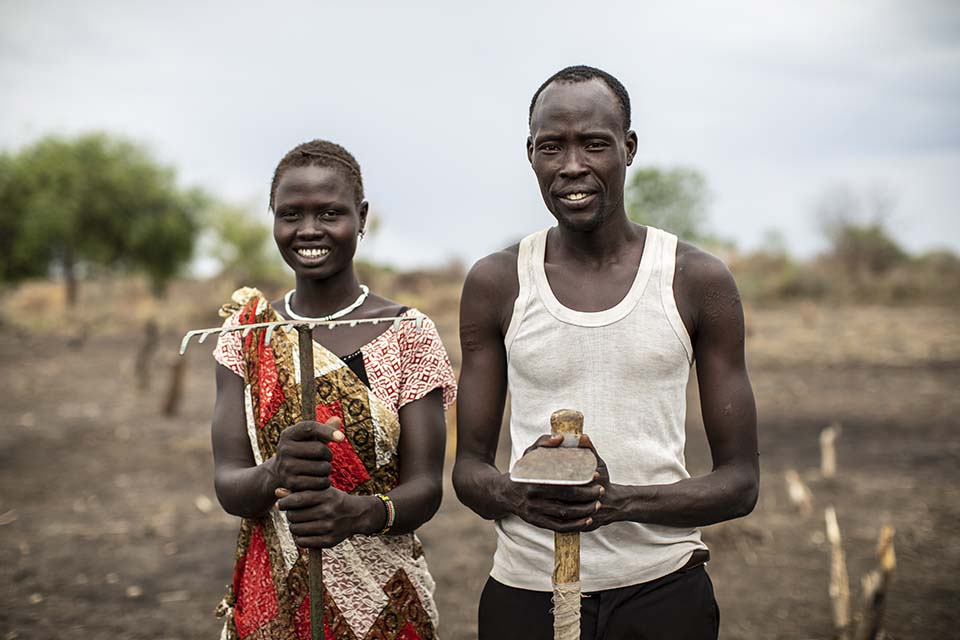 farming couple stand in a field in South Sudan