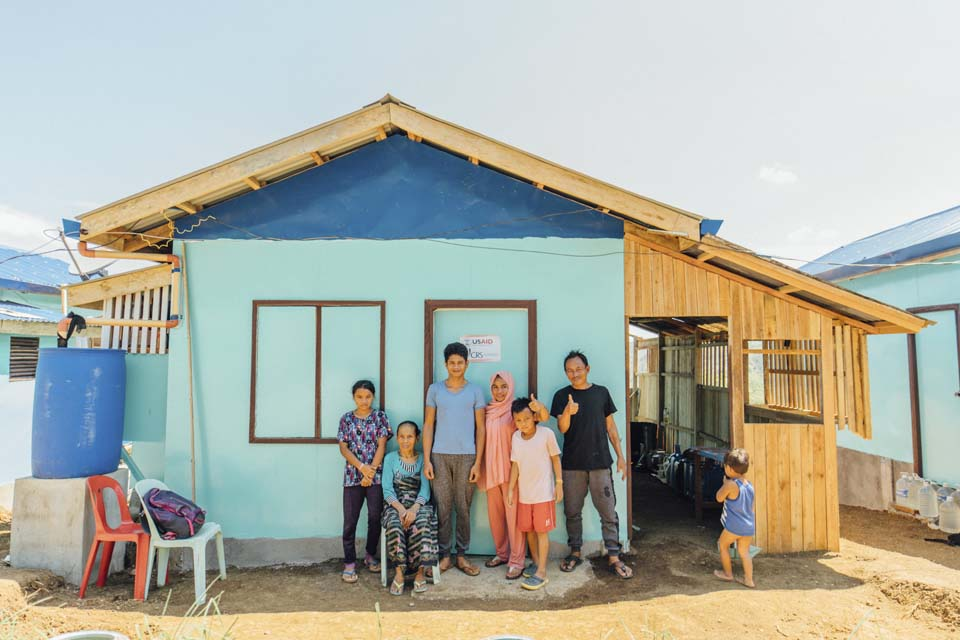 Filipino family outside new shelter