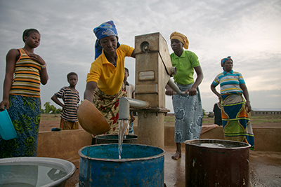 Women in Ghana collect water at a station constructed with support from CRS. Photo by Jim Stipe/CRS
