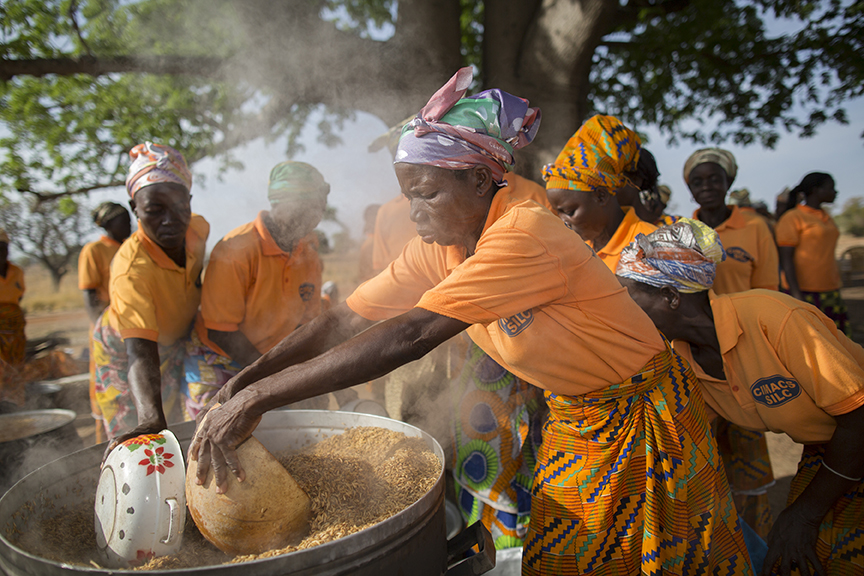 Women in Ghana process rice to capture more of the value of their crop. Photo by Jake Lyell for CRS