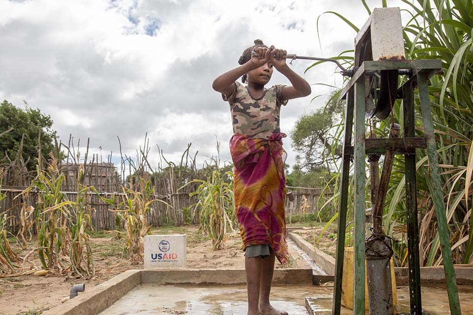 girl at water pump in Mozambique