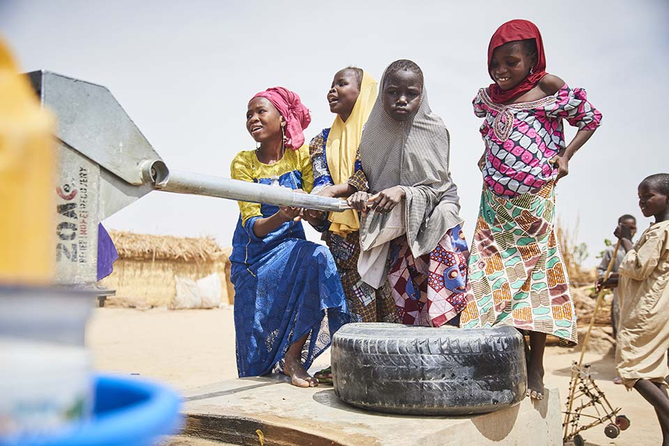 pumping water at Nigerian displaced persons camp