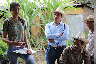 Iris Santos, a technician for Guatemala's coffee association, talks with farmers about how to manage leaf rust. Photo by Silverlight for CRS