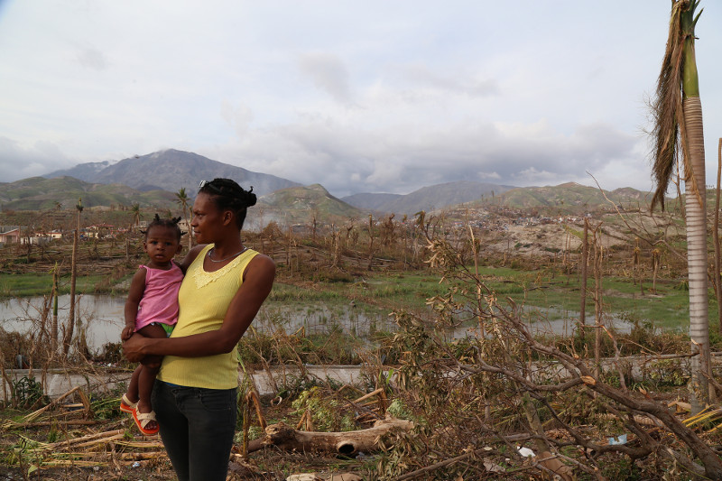A woman named Celine holds her baby, looking toward where her home in Roche a Bateau stood. Roche a Bateau, a town roughly 30 miles southeast of Les Anglaise where the eye of Hurricane Matthew struck, has very few homes standing.