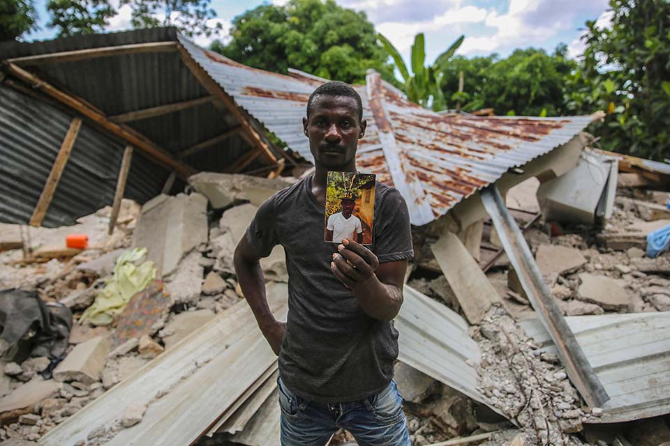 Haiti quake survivor standing near rubble holding photo of lost brother