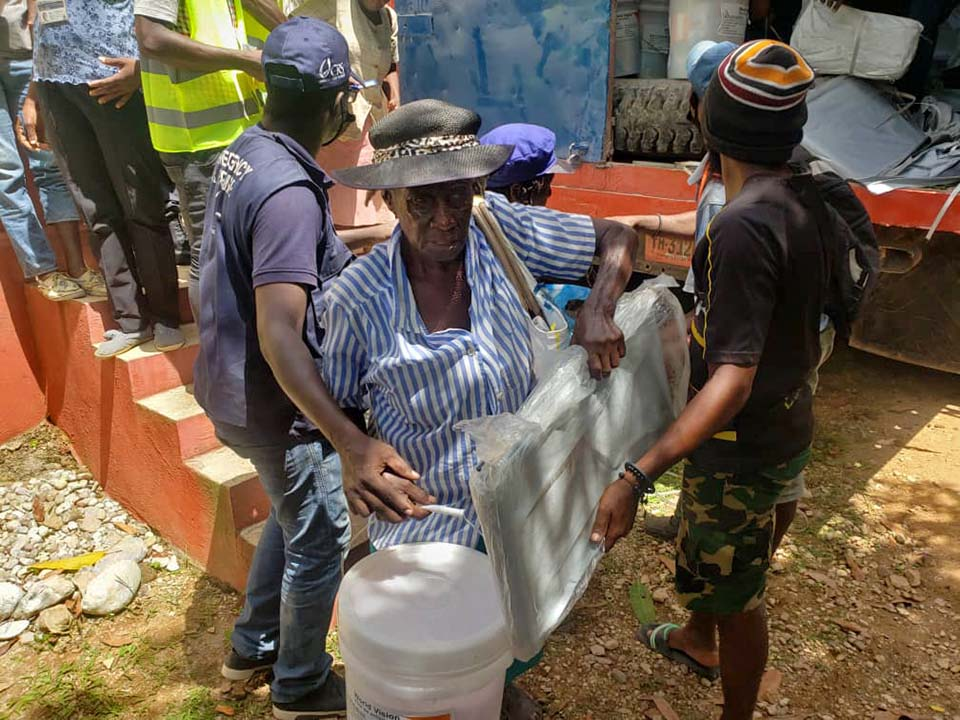 Haitian woman carries supplies at an emergency distribution point