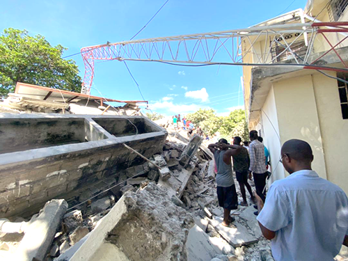 Haitians walk over rubble to survey earthquake damage to buildings