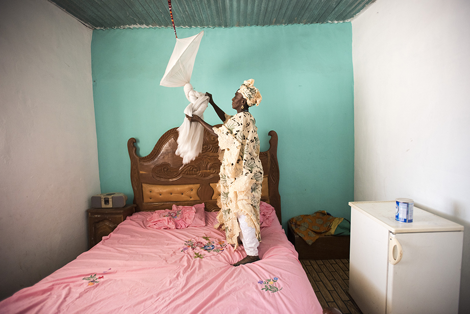 hanging a malaria net in the gambia