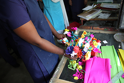 A young woman who survived sex trafficking shows paper flowers she made in Prajwala's print shop. Photo by Laura Sheahen/CRS
