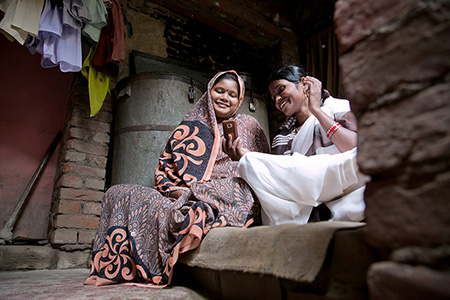 Sunita Devi, right, shares information—via a CRS-developed mobile phone app—that will help Sanchita, pregnant with her fourth child, deliver a healthy baby. Photo by Jennifer Hardy/CRS