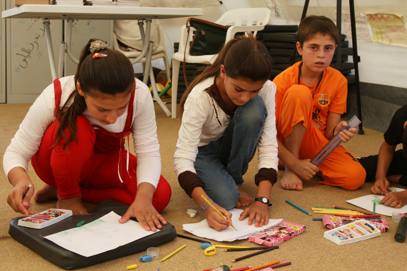 Children participate in activities like writing and drawing at CRS-run child support centers. Photo by Kim Pozniak/CRS