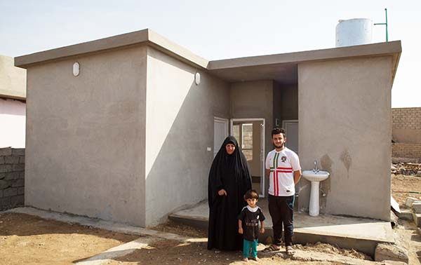 Iraq family stands outside rebuilt home