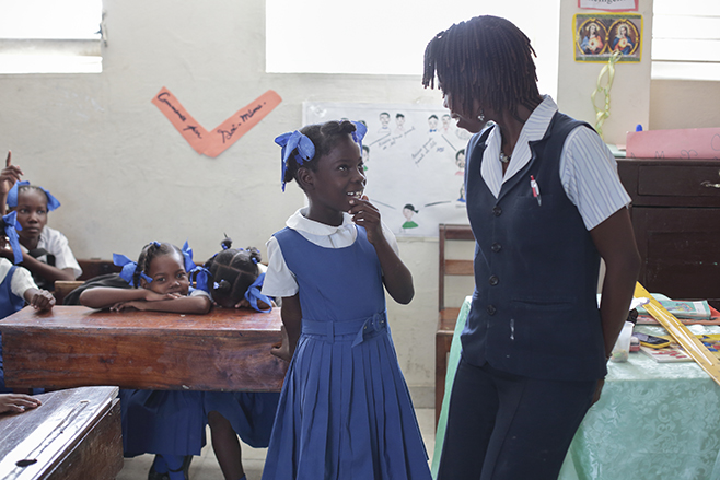 Teacher Maniela Dorcelus speaks with a student at Notre Dame du Saint Esprit Catholic School in Hinche municipality. Catholic Relief Services is supporting education programs in Haiti by training and certifying local school teachers. Photo by Oscar Leiva/
