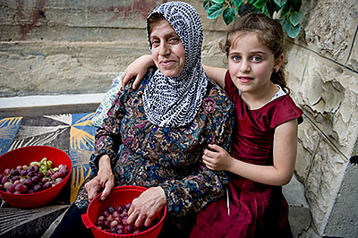 Intisar Atallah enjoys time with her granddaughter in the backyard of her West Bank home. Intisar receives a food voucher through a CRS program. Photo by Karen Kasmauski for CRS